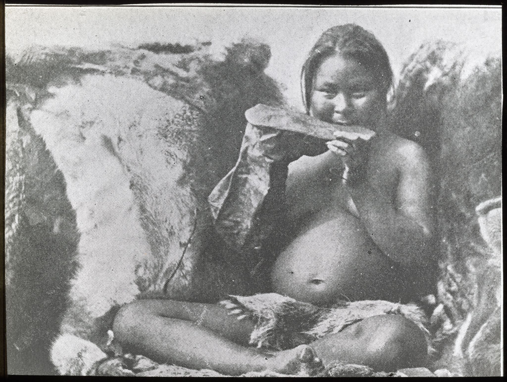 Woman chewing sealskin for boot sole