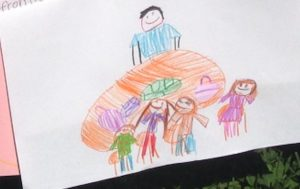 kid's crayon drawing of lunch table with four students and reader