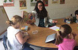 Rebecca Perez reading a picture book in Spanish to elementary school students